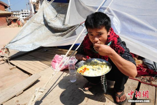 5月4日,受灾严重的尼泊尔加德满都杜巴广场,当地警察继续在被完全震毁的独木庙、Maju dega、Narayan(Bishnu)遗迹上清理废墟,周边受灾民众的生活日渐恢复平静,但仍在简易帐篷里艰难度日。图为受灾小伙在帐篷边吃手抓饭。陈文 摄