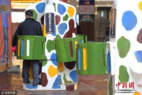 """2017年3月15日,重庆,几座""""男用英式公厕""""亮相洋人街景区路边。这些供男士小便专用的露天公厕,每座有4个站位,仿造英式厕所建造,四面透风,只遮挡住腰部的部分。尽管厕所旁就是通道和游乐设施,不时有男男女女经过,但还是有不少男士使用这些露天公厕如厕,丝毫不介意路人好奇地目光。 左冬辰 摄 图片来源:视觉中国"""