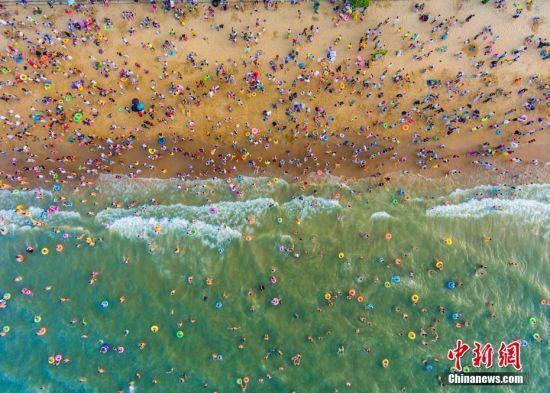 """5月30日,正值中国传统节日端午节,在海南省海口市假日海滩景区汇集众多民众""""洗龙水""""。据官方统计,截至当日18时,共计有19万民众前往假日海滩""""洗龙水"""",海边人头攒动如""""下饺子"""",场面十分壮观。据了解,""""洗龙水""""是海南最有特色的端午节习俗,人们""""洗龙水""""可以得到龙神的保佑,身体健康不长热疮热痱,一年健健康康、平平安安。(航拍图) 中新社记者 骆云飞 摄"""