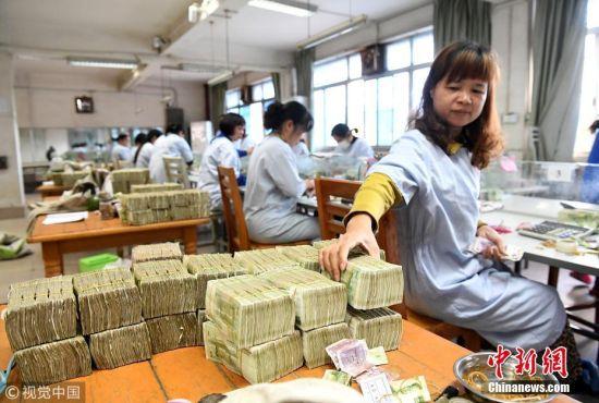 女点钞员将整理好的纸币摆放在一起。黎寒池 摄 图片来源:视觉中国
