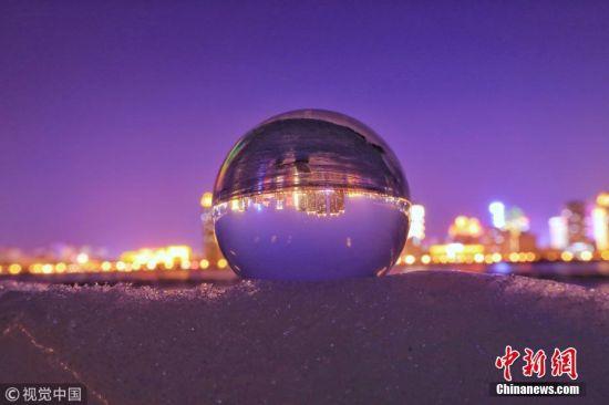 3月4日,黑龙江省哈尔滨市,松花江边,水晶球放在冰面、冰块上,球中倒影着冰城美丽的影像。图片来源:视觉中国