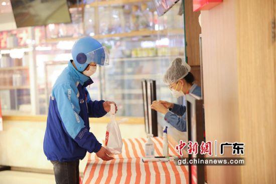 外送员在餐饮店取餐。付宝华摄影。
