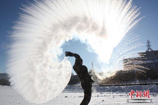 12月6日,黑龙江伊春最低气温达到零下33度。伊春边防支队新兵在训练之余,玩起泼水成冰游戏。中新社发 李广福 摄